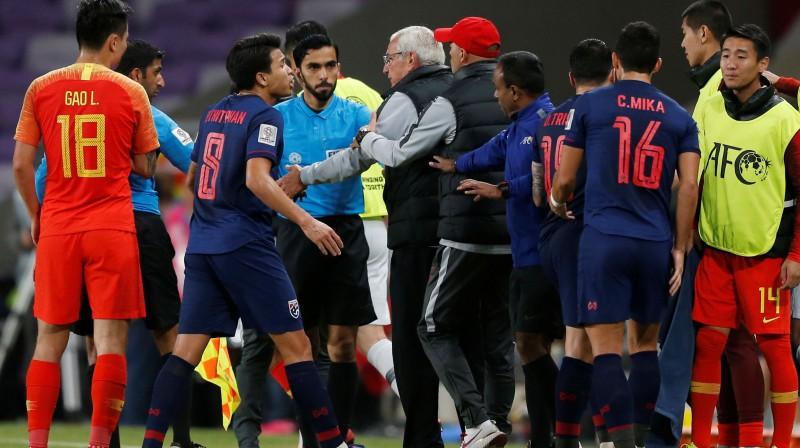 Ķīnas futbola izlases galvenais treneris Marselo Lipi iziet laukumā pēc spēlētāju nekārtībām. Foto: Reuters/Scanpix