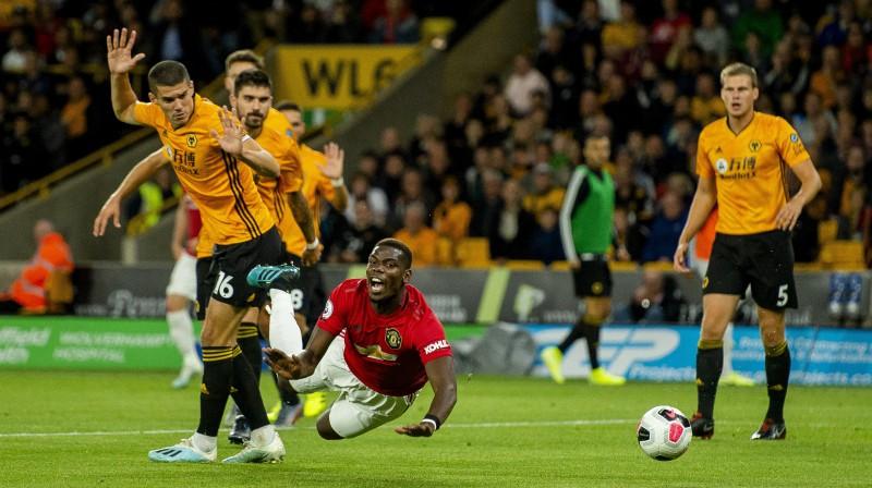 """Mančestras """"United"""" futbolists Pols Pogbā krīt Vulverhemptonas """"Wanderers"""" soda laukumā. Foto:"""