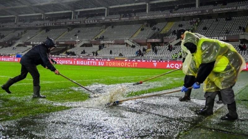 """Darbinieki tīra pielijušo laukumu pirms """"Torino"""" un """"Inter"""" spēles Turīnā. Foto: AFP/Scanpix"""