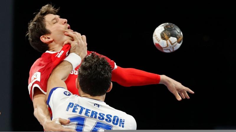 Aleksandrs Pētersons izdara rupju pārkāpumu pret Šveices izlases handbolistu. Foto: AFP/Scanpix